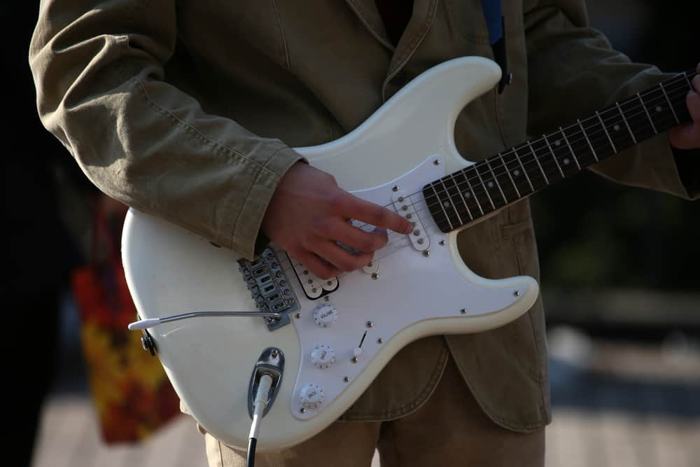 A close look at an electric guitar being played.