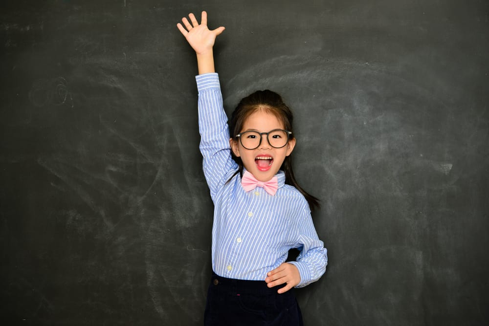 A girl raises her hand to ask a question.