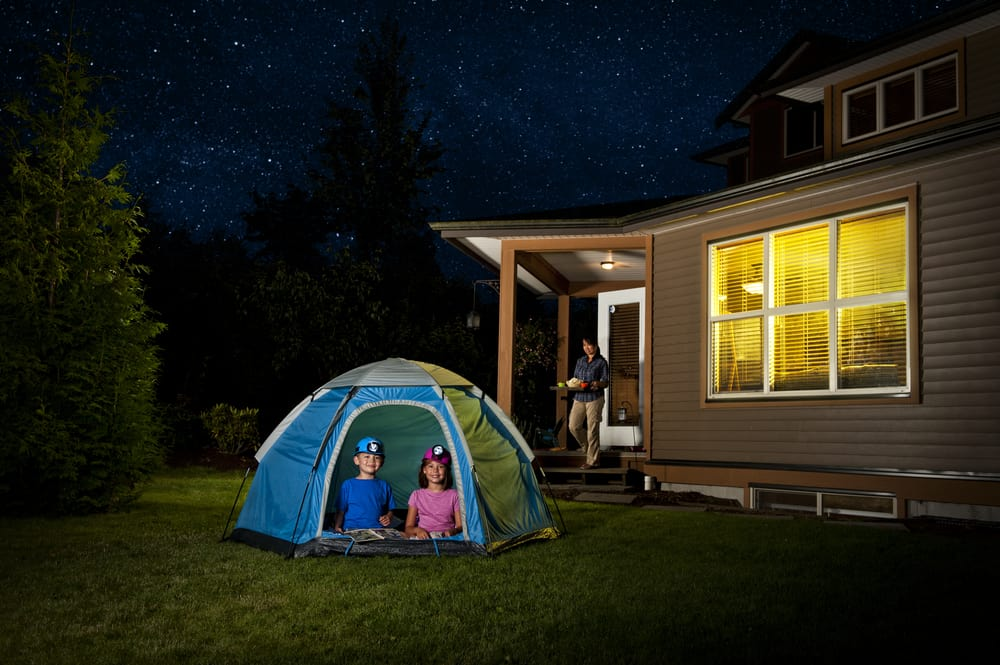 A couple of kids camping in a tent at the backyard.