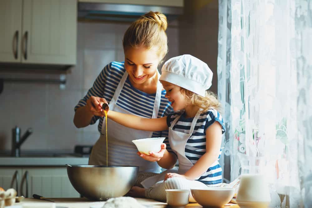 Mother and daughter baking together in the kitchen.
