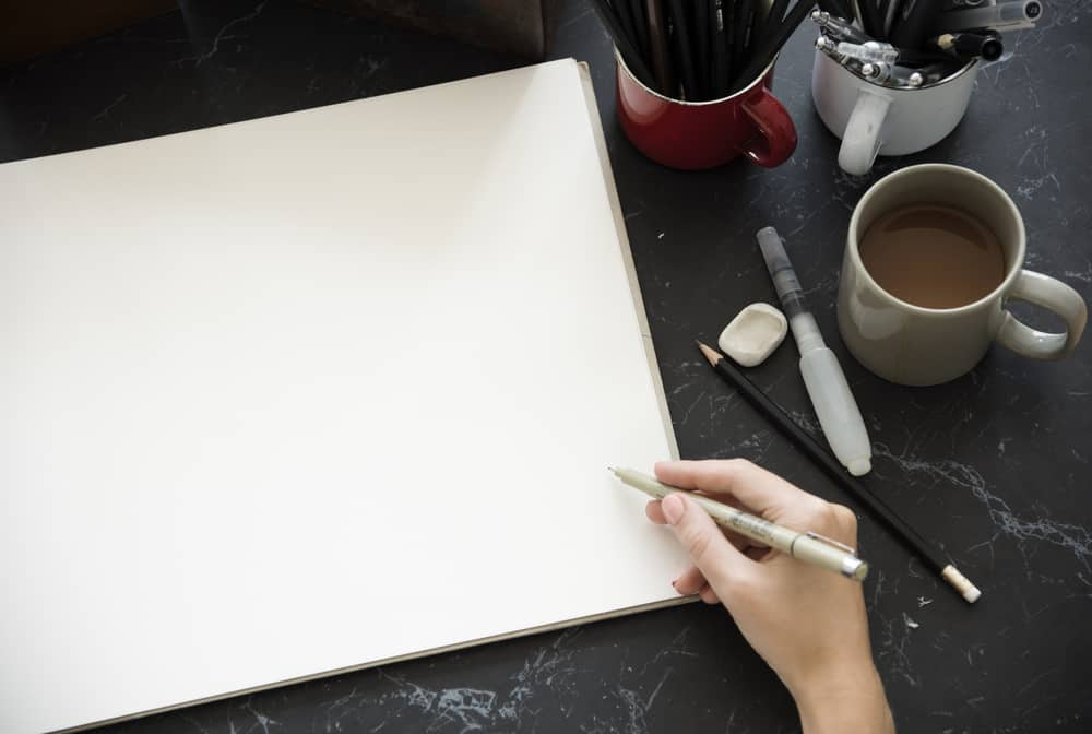 A person about to sketch on the piece of paper.