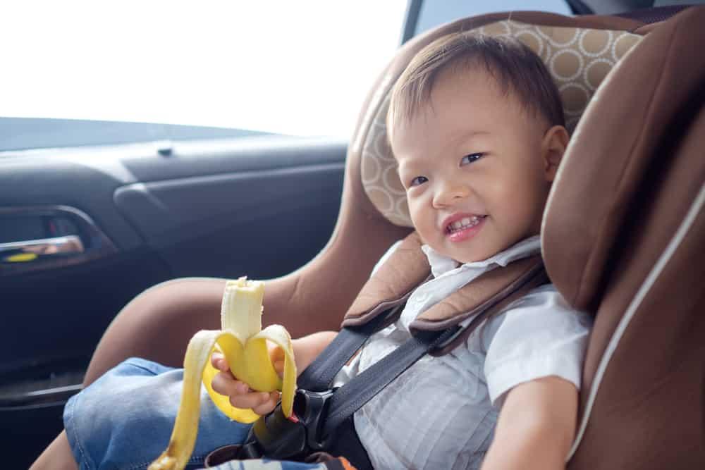 A toddler eating a banana inside the car.