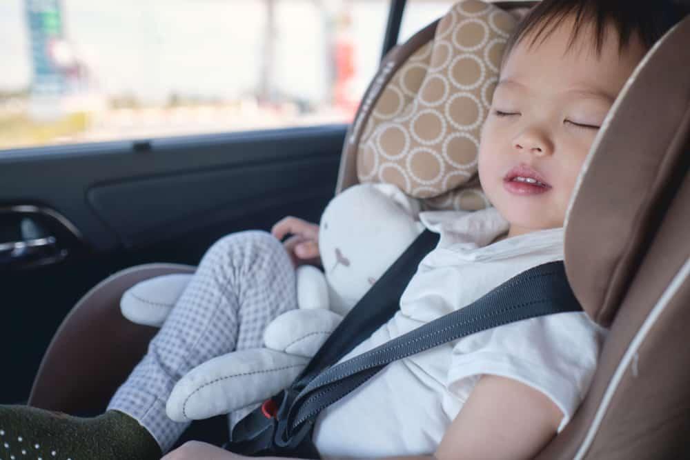 A toddler sleeping inside the car.