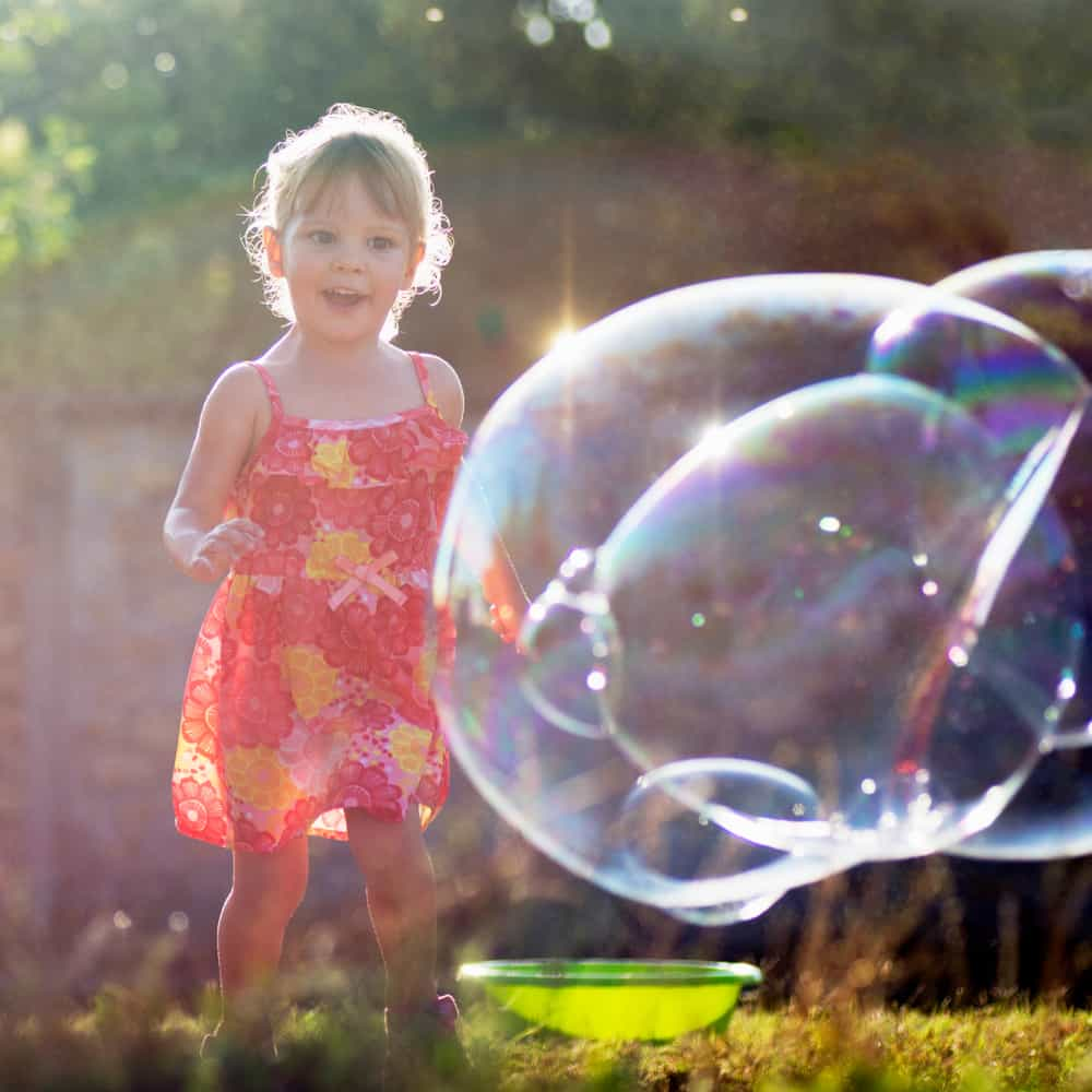 A girl chasing and playing with bubbles.