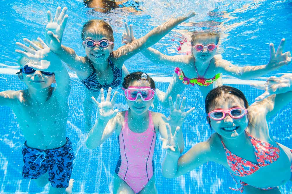 A group of kids swimming in the pool.
