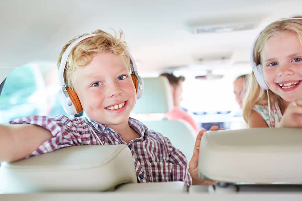 Siblings listening to a podcast in the backseat.