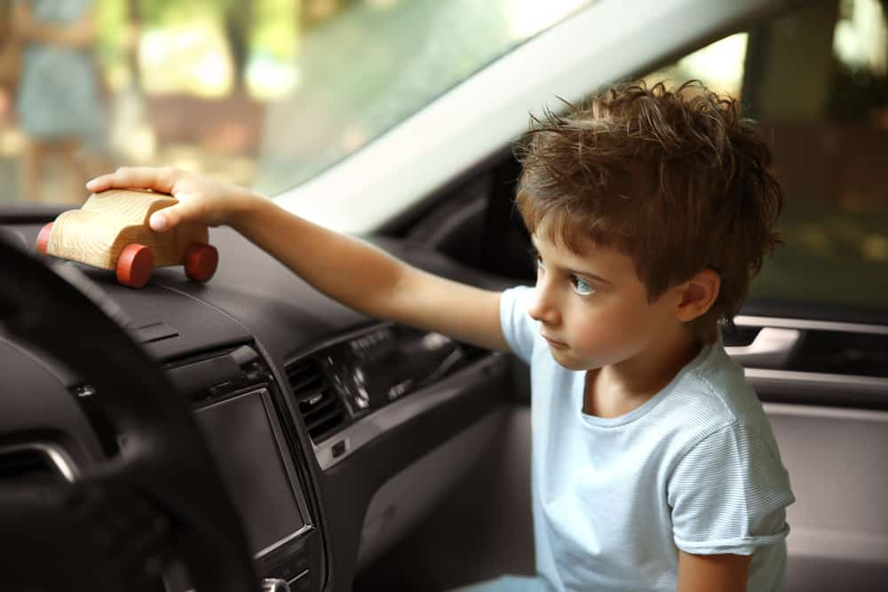 A kid playing with a wooden toy car at the passenger seat.