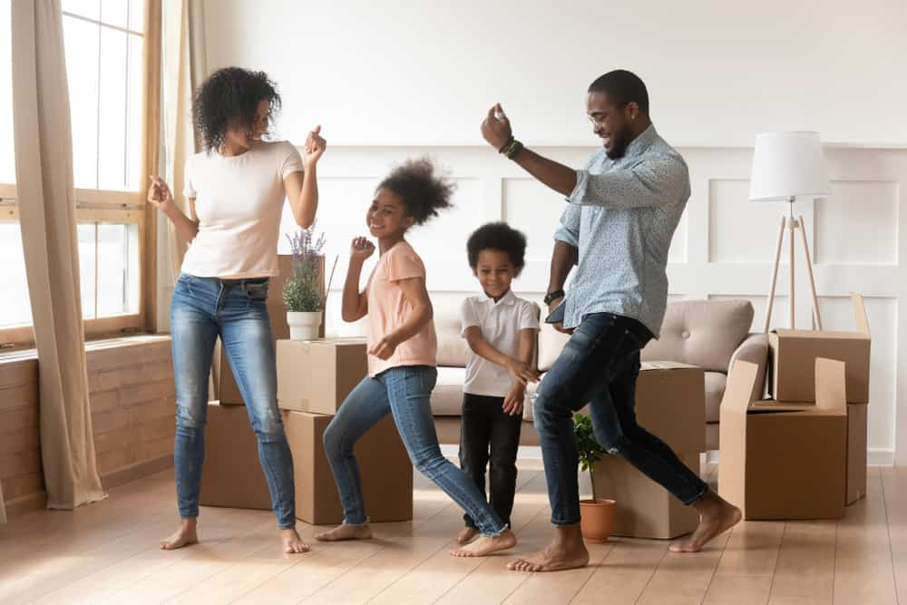 A family dancing together in the living room.