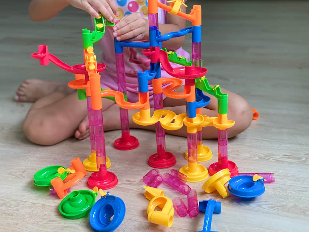 A kid making a marble run track with plastic parts.