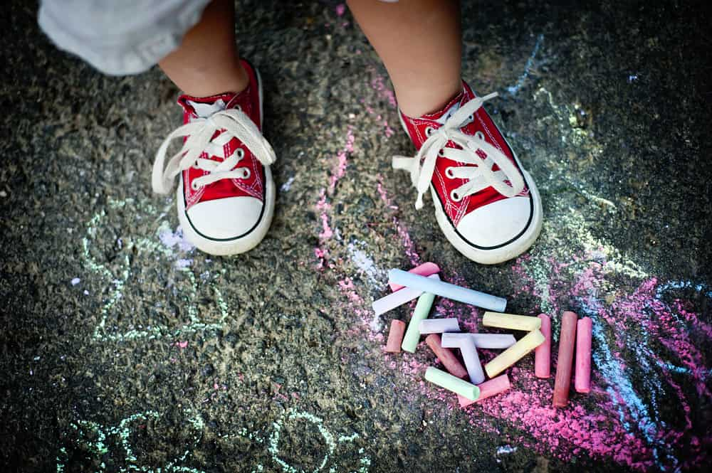 A toddler wearing a pair of canvas shoes.