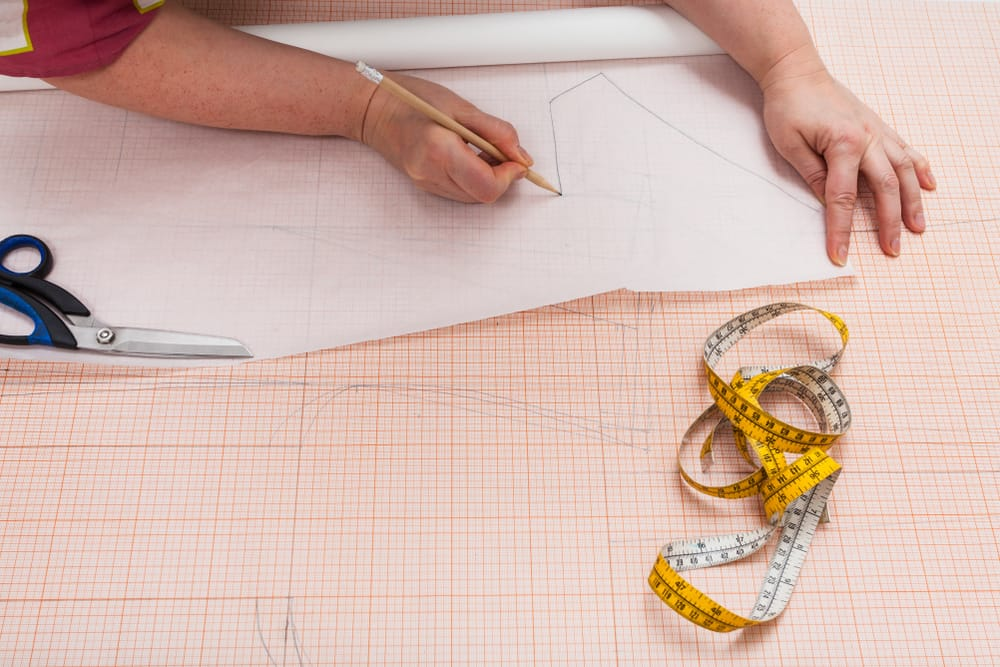 A close look at a tailor using tracing paper.