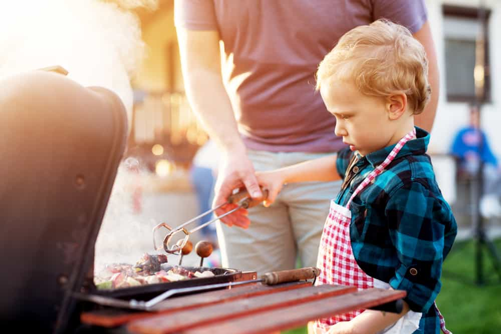 A toddler cooking on the grill with a parent.
