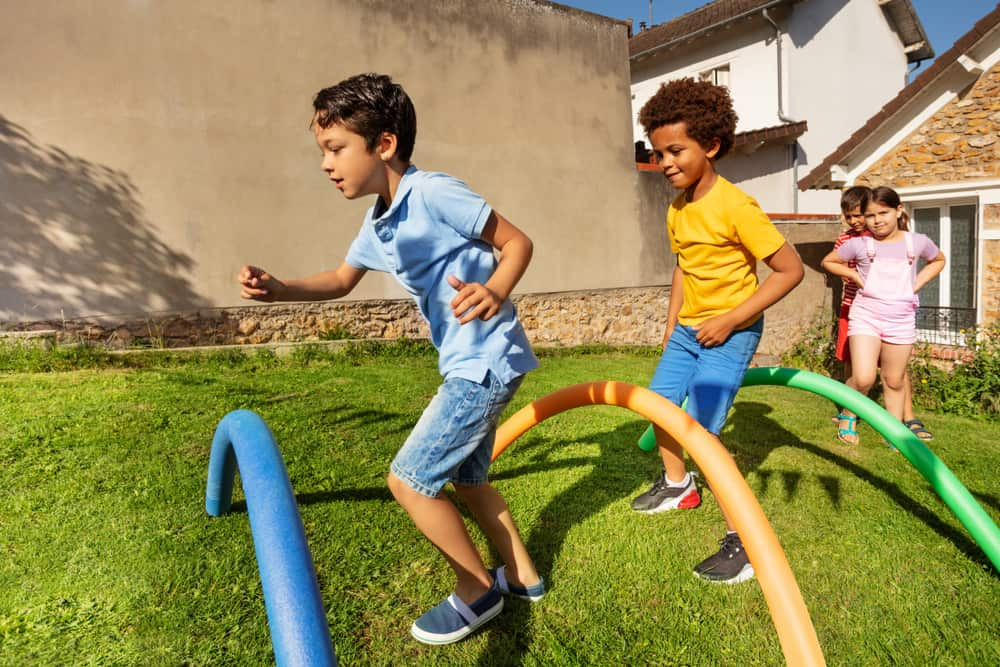A group of kids playing on the obstacle course.