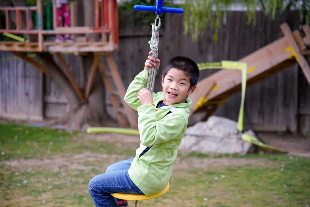 A boy playing on the zip line in the backyard.