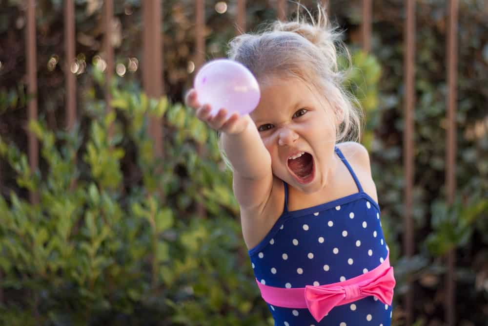 A girl playing with a water balloon in the backyard.
