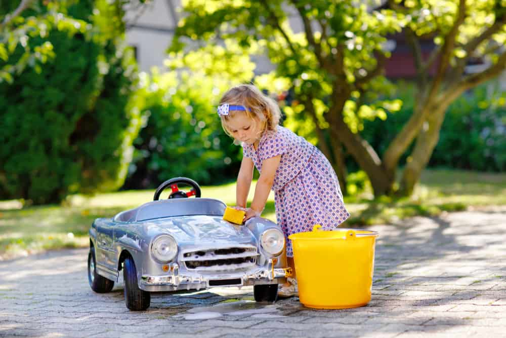 A girl cleaning her toy car in the backyard.