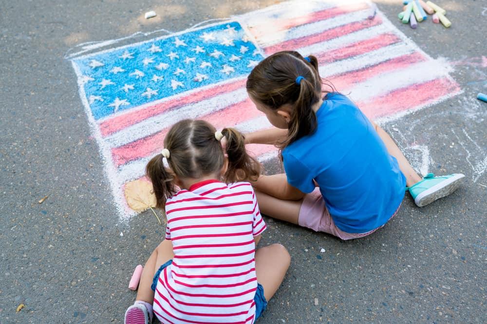 Two kids doing chalk artwork on the concrete floor.