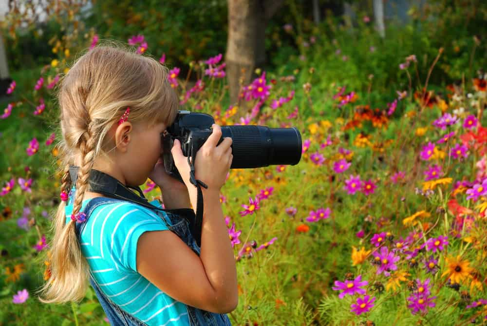 A girl taking photos of flowers with a professional camera.