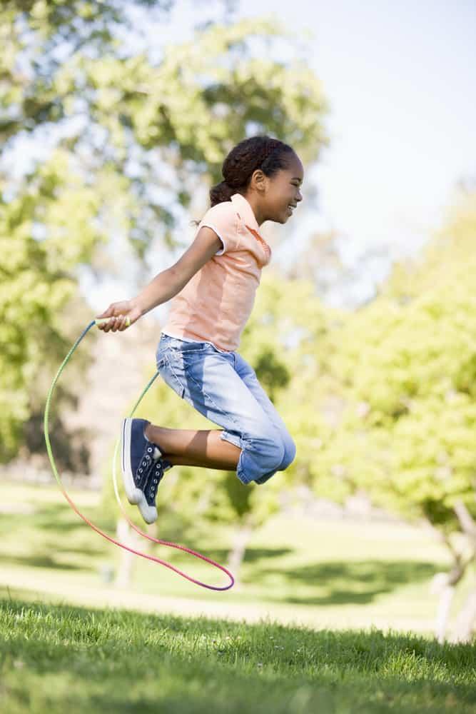 A girl playing jump rope at the backyard.