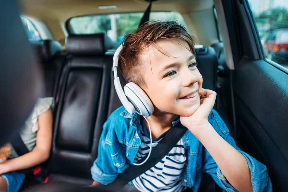 A happy boy wearing headphones listening to audiobooks.