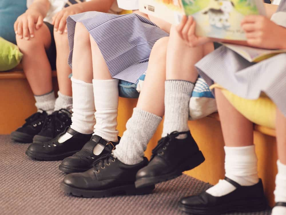 A close look at a row of school children wearing leather shoes.