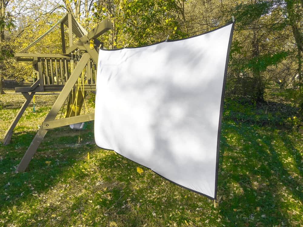 A projector screen setup in the backyard.