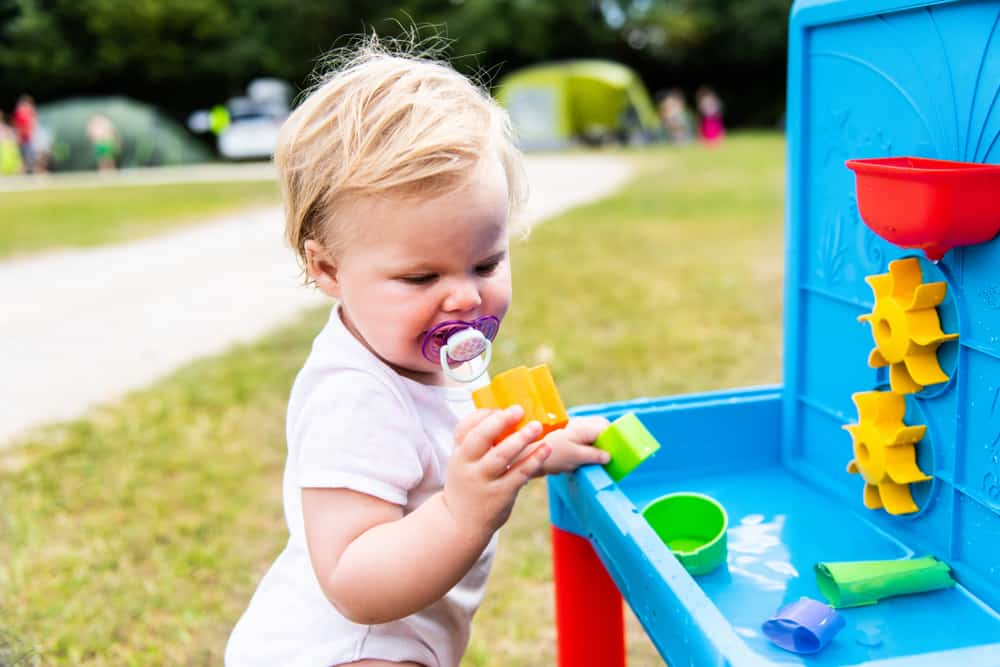 A toddler playing with a plastic water table toy.