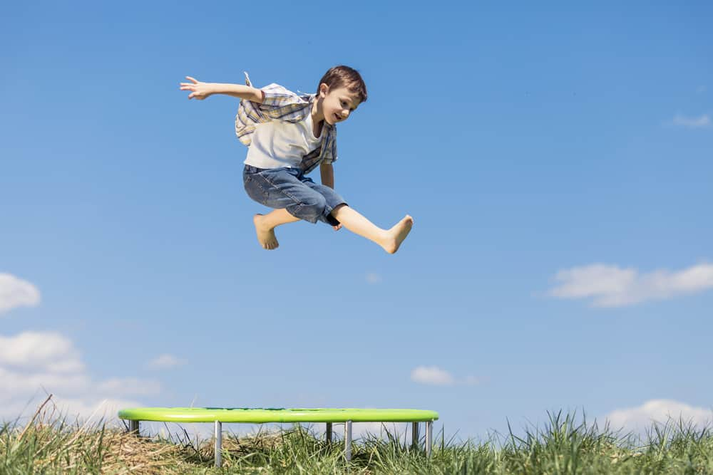 A boy playing on the trampoline on the grass lawn.