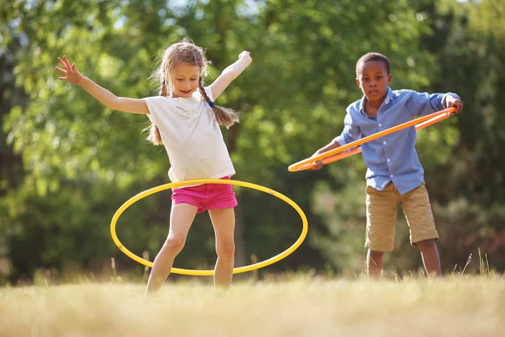 A boy and a girl playing with hoola hoops.