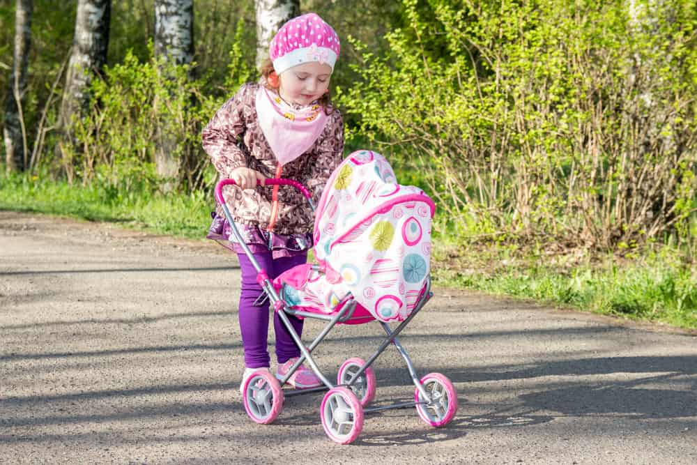 A girl playing with her baby doll on a stroller.