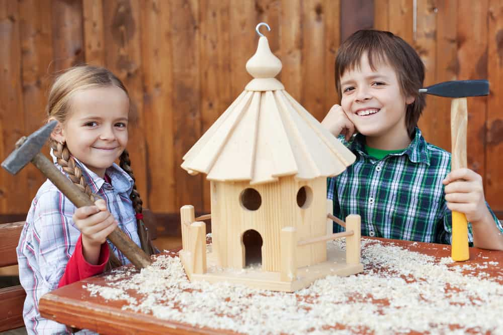 Two kids showing off the bird house they made.