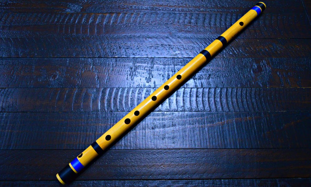 This is a bansuri flute on a hardwood flooring.