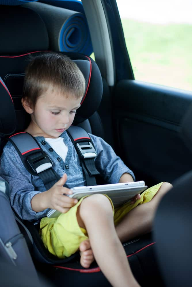 A boy playing with his tablet in the car.