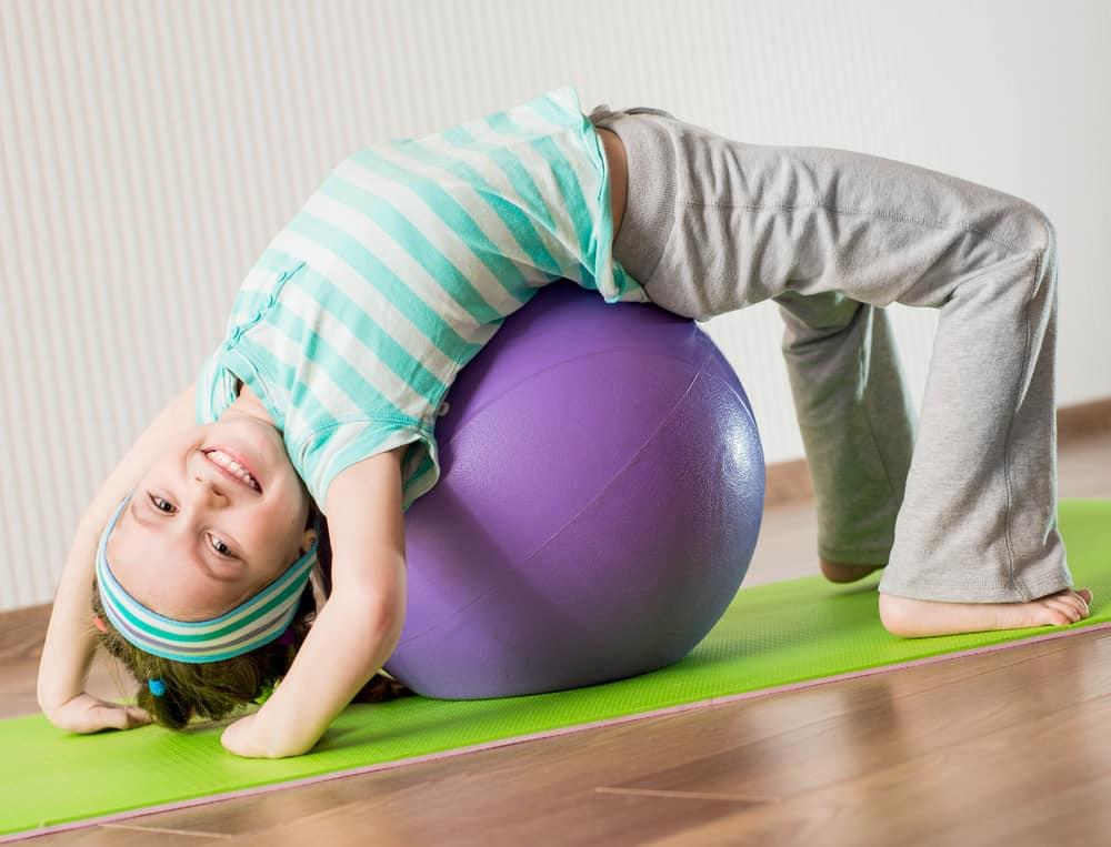 A girl playing on a yoga ball.