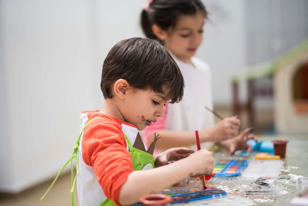 A couple of kids making crafts together with the use of watercolor paint.