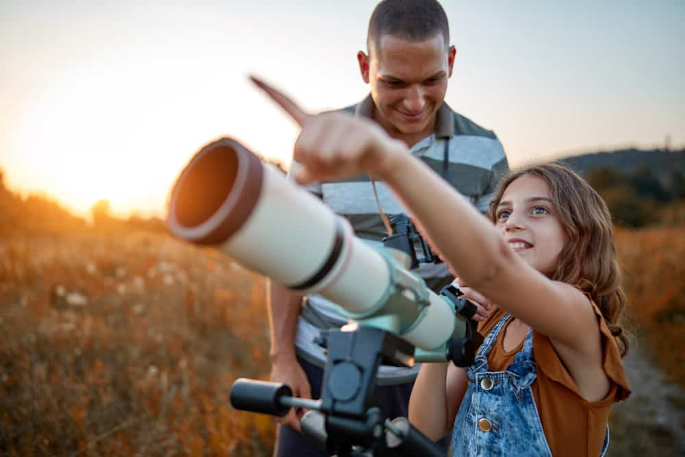 A father and daughter using a telescope to gaze at stars.