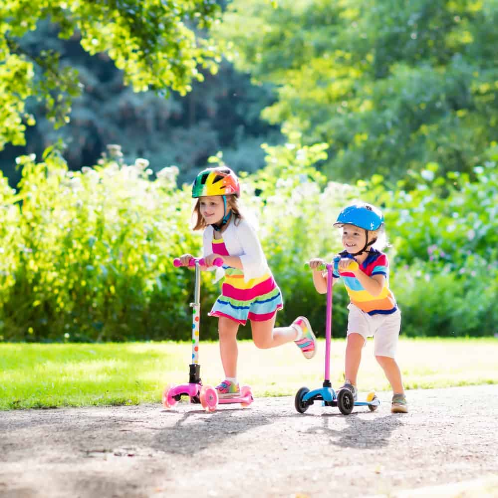 Two girls riding on scooters at the park.