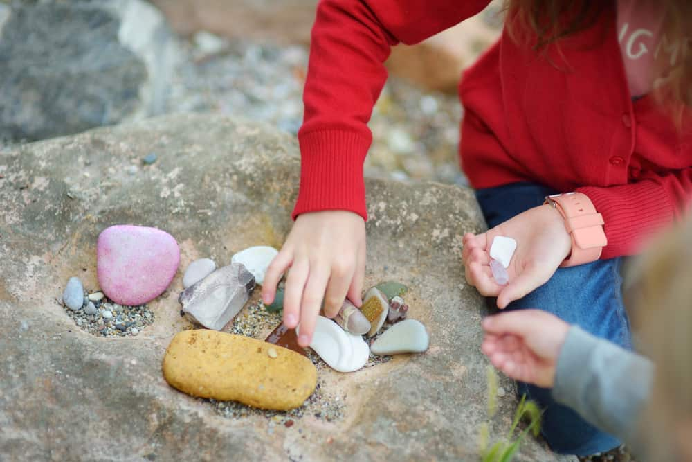Two kids collecting various colorful rocks.