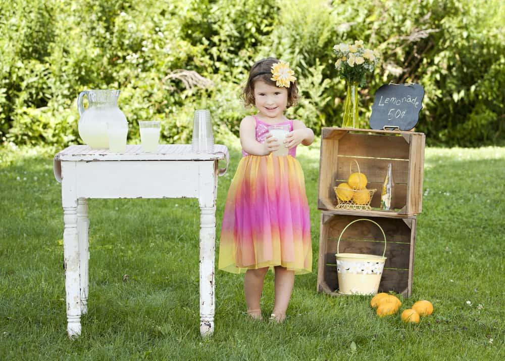 A little girl selling lemonade at her lemonade stand.