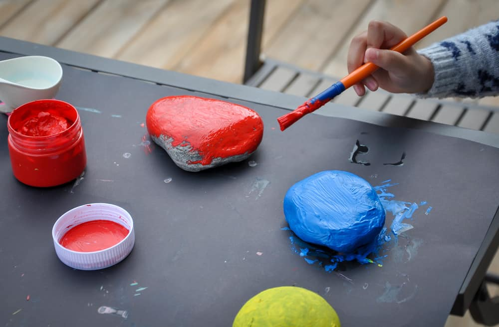 This is a close look at a kid painting rocks.