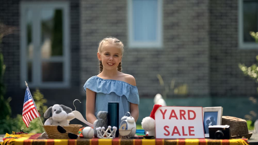 A girl selling items at a yard sale.