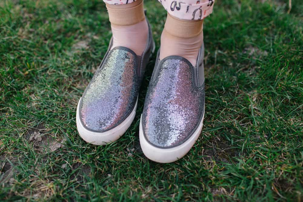 A pair of colorful and sparkly slip-on shoes.