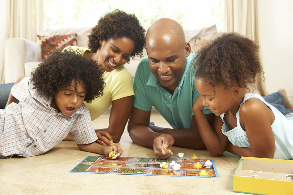 A family on the floor playing a board game together.