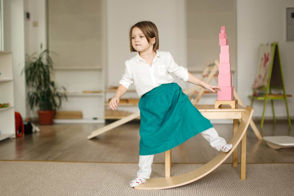 A girl playing on a wooden balance board.