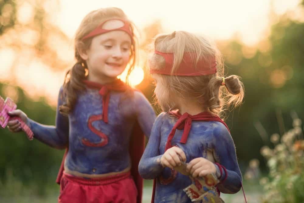 A couple of girls wearing superhero costumes.