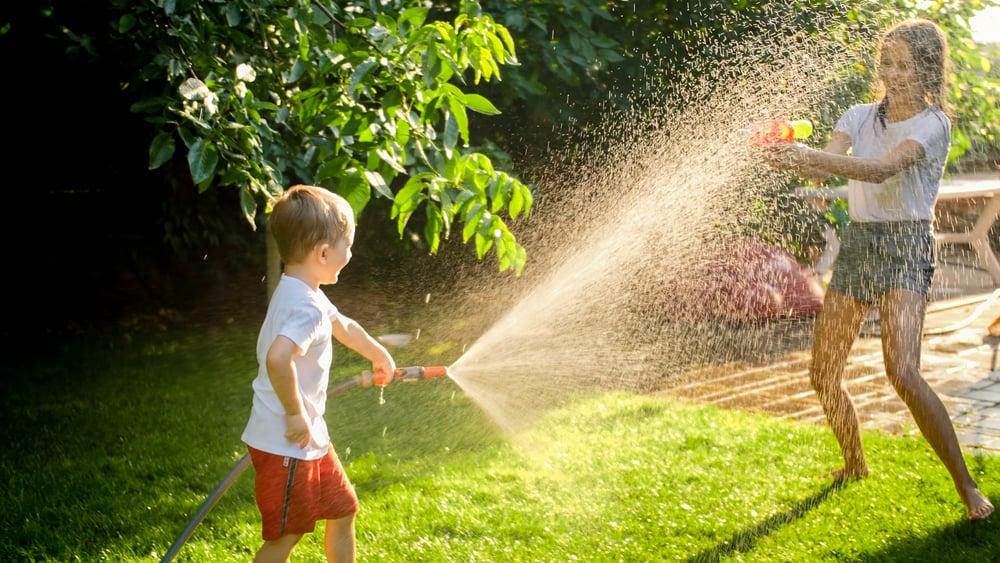 Siblings having a water fight in the backyard.