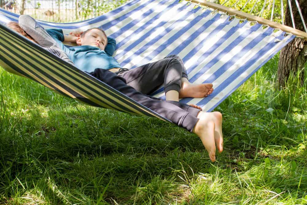 A couple of kids sleeping on the hammock.