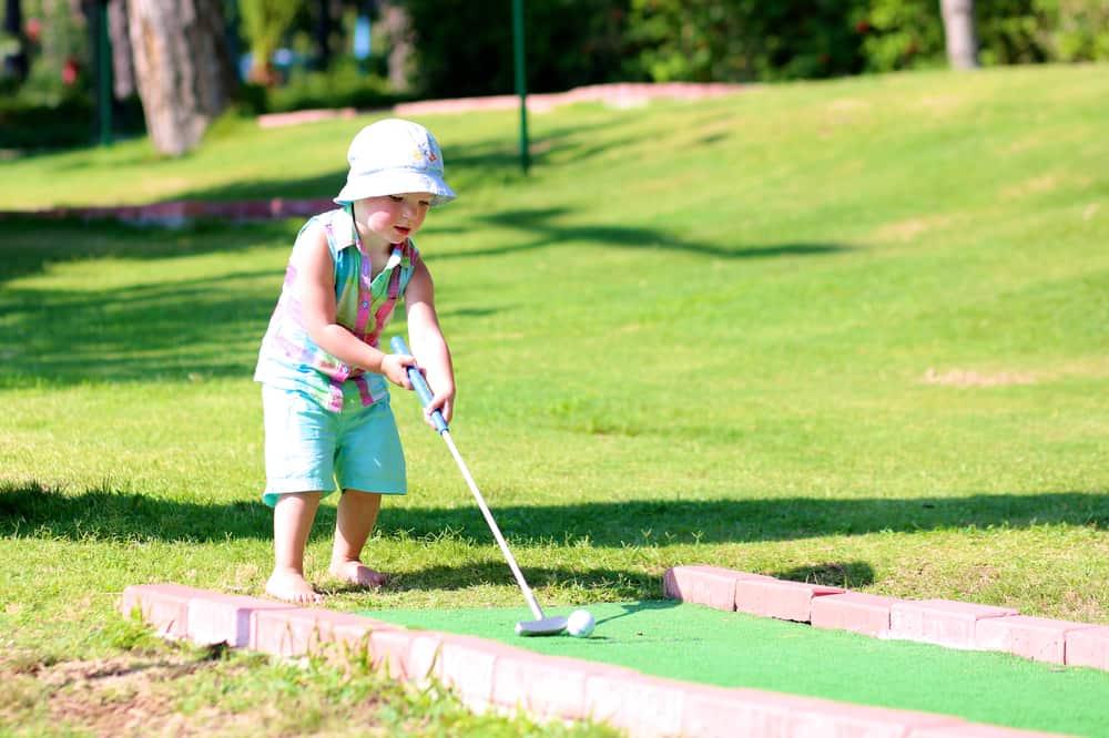 A toddler playing miniature golf.