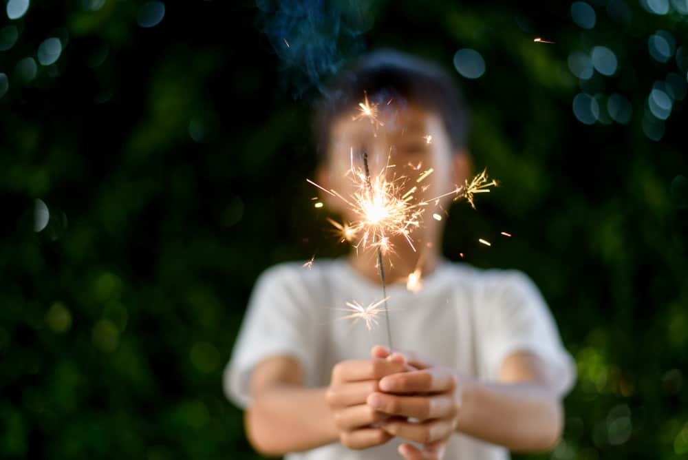 A boy playing with sparklers at the backyard.