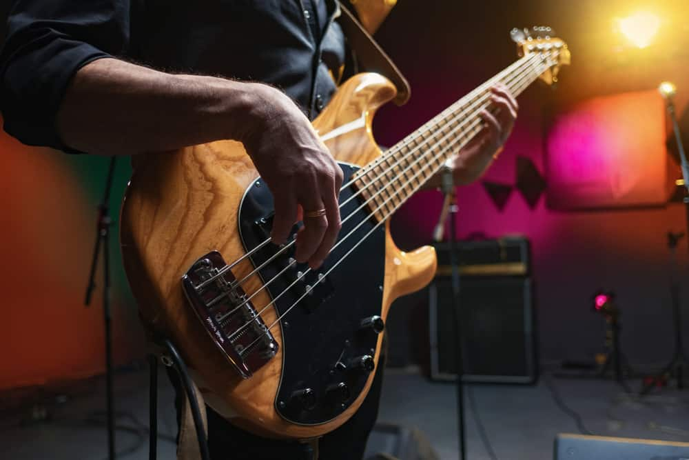 A close look at a bass guitar being played.
